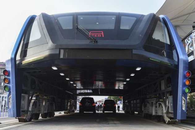 """It may look like something from the future, but China's long-awaited """"straddling bus"""" ran its inaugural test in Hebei province this week. The 2m-high Transit Elevated Bus (TEB) straddles the cars below, allowing them to pass through. Powered by electricity, the bus is able to carry up to 300 passengers in its 72ft (21m) long and 25ft wide body. (Image: AP)"""